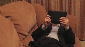 Бизнесмен лежа на кресле и читая таблетку видеоматериал
