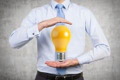 Бизнесмен держа лампу Стоковое Изображение