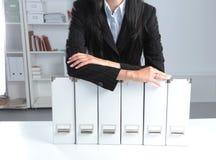 Бизнесмен держа архивы данных на связывателе shelves предпосылка Стоковое Изображение