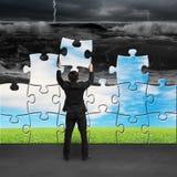 Бизнесмен держа головоломки к собранию поворачивая плохую ситуацию Стоковые Изображения