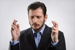 Бизнесмен держа его пальцы пересеченный. Бизнесмен стоя wi стоковое изображение rf
