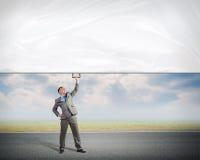Бизнесмен держа знамя с одной рукой Стоковая Фотография