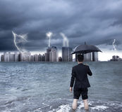 Бизнесмен держа зонтик с ливнем с грозой Стоковая Фотография RF