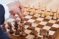 Бизнесмен держа диаграмму шахмат пока играющ шахмат самостоятельно Стоковые Изображения
