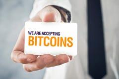 Бизнесмен держа карточку с названием МЫ ПРИНИМАЕМ BITCOINS Стоковое Изображение