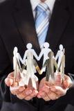 Бизнесмен держа команду металла в приданных форму чашки руках Стоковые Изображения