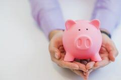 Бизнесмен держа копилку в его символе рук сбережений и хороших инвестиций Стоковое Фото