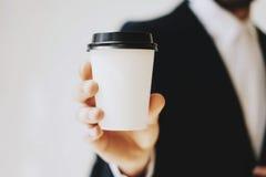 Бизнесмен держа кофейную чашку белой бумаги для того чтобы принять прочь Насмешка вверх чистой кофейной чашки коробки Горизонталь Стоковые Изображения