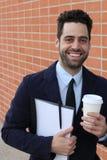 Бизнесмен держа кофейную чашку и папку с усмехаться документов стоковые фото