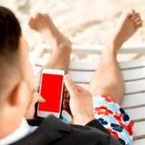 Бизнесмен держа мобильный телефон на пляже Стоковое Фото