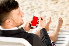 Бизнесмен держа мобильный телефон на пляже Стоковое Изображение RF