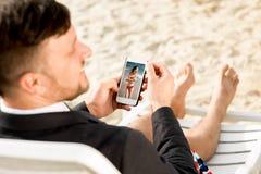 Бизнесмен держа мобильный телефон на пляже Стоковое фото RF