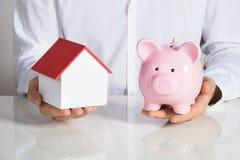 Бизнесмен держа модель и Piggybank дома Стоковое Изображение