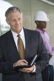 Бизнесмен держа молокозавод с мужским архитектором Стоковые Фото