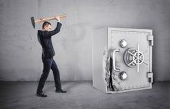 Бизнесмен держа молоток над его головой, и сейфом при своя сломанная дверь стоковые фотографии rf