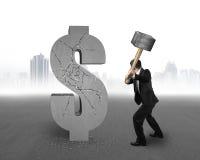 Бизнесмен держа молоток ударяя треснутый знак доллара с городом Стоковое фото RF