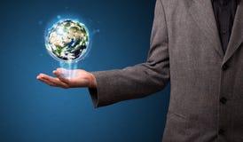 Бизнесмен держа накаляя глобус земли Стоковые Фото