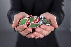 Бизнесмен держа обломоки покера в приданных форму чашки руках Стоковое Фото