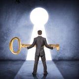 Бизнесмен держа огромный ключ золота, вид сзади стоковые изображения