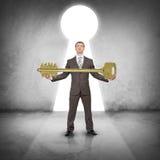 Бизнесмен держа огромный ключ золота Стоковые Изображения