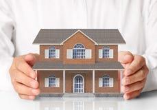 Бизнесмен держа домашнюю модель Стоковые Фото