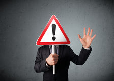 Бизнесмен держа дорожный знак возгласа Стоковое Изображение