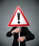 Бизнесмен держа дорожный знак возгласа Стоковая Фотография RF