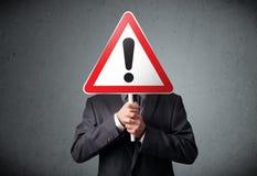 Бизнесмен держа дорожный знак возгласа Стоковые Фото