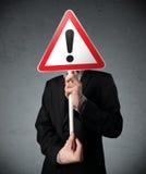 Бизнесмен держа дорожный знак возгласа Стоковые Изображения RF