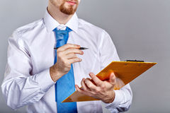 Бизнесмен держа папку и ручку Стоковое Фото