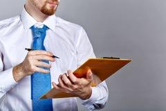 Бизнесмен держа папку и ручку Стоковые Изображения RF