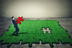 Бизнесмен держа последнюю часть нося зеленой головоломки Стоковое Фото
