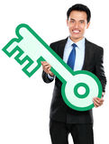 Бизнесмен держа символ ключей стоковое фото rf