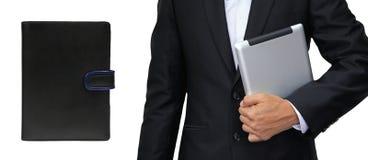 Бизнесмен держа таблетку против книги организатора изолированный Стоковое Изображение