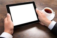 Бизнесмен держа таблетку с изолированным экраном над виллой стоковые изображения