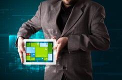 Бизнесмен держа таблетку с sy самомоднейшего програмного обеспечения рабочее Стоковые Изображения