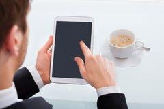 Бизнесмен держа таблетку цифров в офисе Стоковое Фото