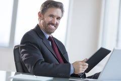 Бизнесмен держа таблетку цифров на столе Стоковые Фото
