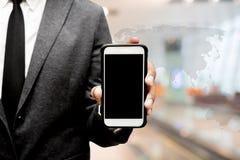Бизнесмен держа умный телефон с изображением нерезкости пути залы стоковые изображения
