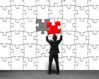 Бизнесмен держа уникально красную головоломку собирая к белой головоломке Стоковые Изображения
