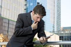 Бизнесмен держа цифровую таблетку стоя outdoors работающ outdoors финансовый район Стоковые Фото