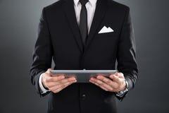 Бизнесмен держа цифровую таблетку Стоковые Фото