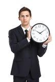 Бизнесмен держа часы стоковая фотография