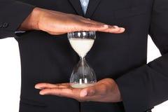 Бизнесмен держа часы Стоковые Изображения