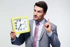 Бизнесмен держа часы Стоковое Фото