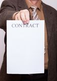 Бизнесмен держа чистый лист бумаги с подписывает контракт Стоковое фото RF