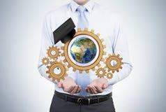 Бизнесмен держа шестерни Стоковая Фотография