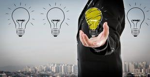 Бизнесмен держа электрическую лампочку Стоковые Фото