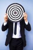 Бизнесмен держа dartboard Стоковые Изображения