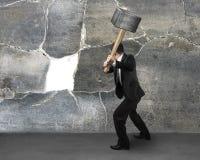 Бизнесмен держа sedgehammer для того чтобы треснуть стену Стоковое фото RF